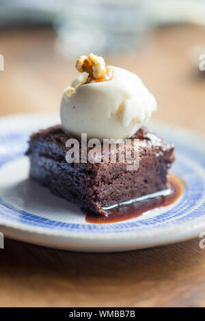 Close-up Of Chocolate Brownie With Vanilla Ice Cream In Plate On Table - Stock Photo