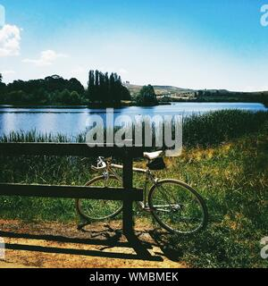 Bicycle Parked On Grassy Lakeshore Against Sky - Stock Photo