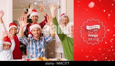 Happy extended family in santa hat cheering at camera against red vignette - Stock Photo