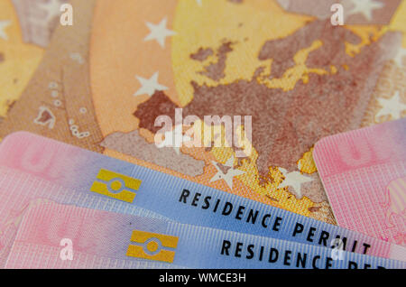 UK Biometrical Residence Permit cards and a map of the EU on the Euro banknote. Concept photo for immigration. - Stock Photo
