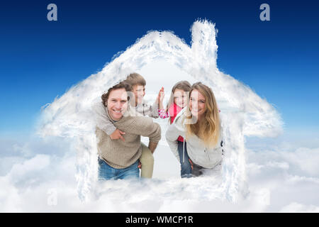 Happy couple piggybacking kids at beach against blue sky over clouds - Stock Photo