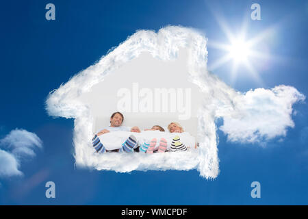 Family wearing stripey socks against bright blue sky with clouds - Stock Photo