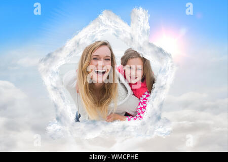 Couple piggybacking kids at the beach against blue sky with white clouds - Stock Photo