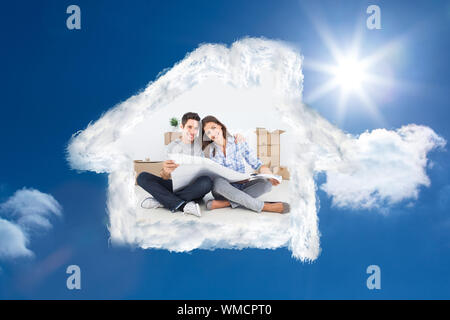 man and woman holding house plans  against bright blue sky with clouds - Stock Photo