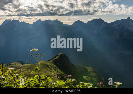 Sunrays break through cloud cover shining on mountains - Stock Photo
