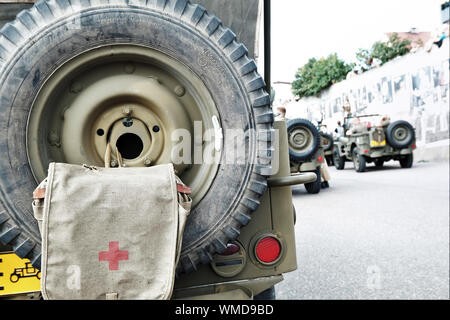 back of historic military vehicle with first aid kit attached to the wheel at 'D-day Hel' a historical reenactment festival in Hel, Pomerania, Poland. - Stock Photo