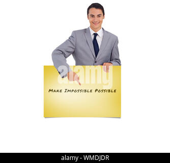 Goodlooking man holding and pointing at a big poster against yellow card - Stock Photo