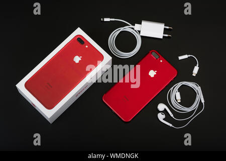 BURGAS, BULGARIA - AUGUST 7, 2018: Apple iPhone 7 Plus Red Special Edition on black background, back side. Charger, earpods and adapter. - Stock Photo
