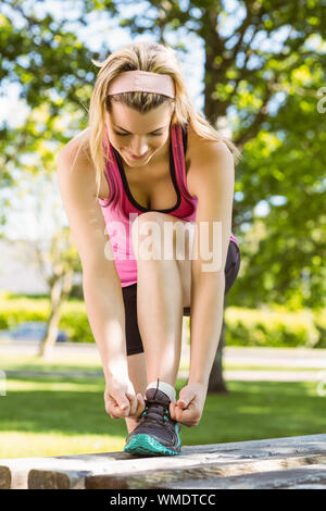 Fit blonde tying her shoelace on a sunny day - Stock Photo