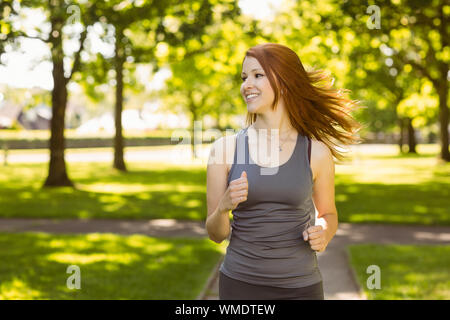 Portrait of a pretty redhead running on a sunny day - Stock Photo