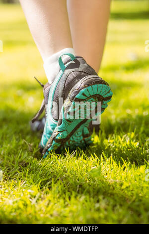Woman in running shoes stepping on grass on a sunny day - Stock Photo