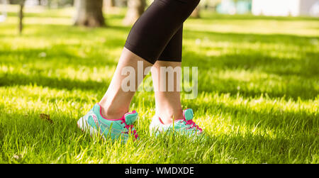 Woman in running shoes stepping on grass in the park - Stock Photo