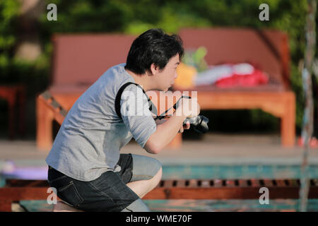 The moment of Asian Thai Professional photographer is kneeling and wating for take a great photo. - Stock Photo