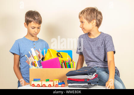 Donation concept. Kids with donate box with books and school supplies, clothes and toys on white desk - Stock Photo