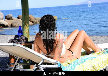 Young Tattooed Woman Sunbathing On Lounge Chair At Beach During Summer - Stock Photo