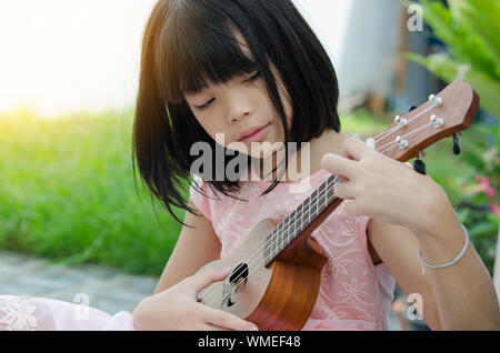A little girl playing ukulele in the garden. - Stock Photo