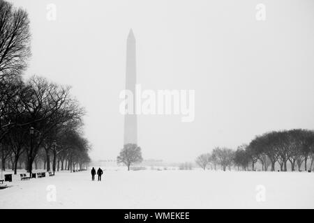 People Walking On Snow In Park With Washington Monument Under Foggy Weather Against Sky - Stock Photo