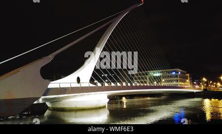 Illuminated Samuel Beckett Bridge Over Liffey River At Night - Stock Photo