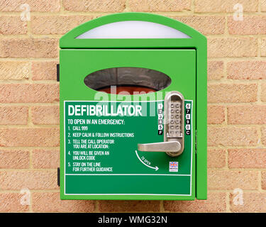 Automated External Defibrillator Mounted on the Wall of a Village Hall, Stanford in the Vale, Oxfordshire, United Kingdom - Stock Photo