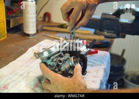 motorcycle carburetor. Automotive Carburetor Repair. Male Using A tong To Rebuild A Carburetor On A Workbench. Mechanic man checking carburetor - Stock Photo