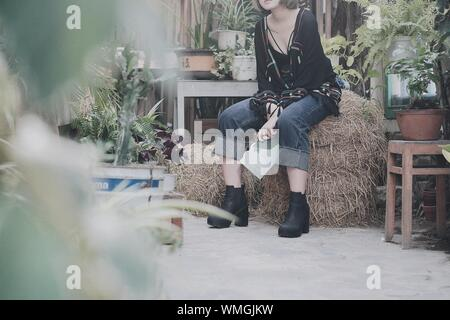 Woman Sitting On Hay Bale Against Building - Stock Photo