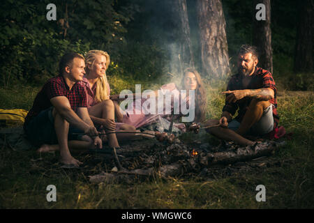 Group of friends camping in forest. Two couples frying sausages on sticks. Youngsters talking around campfire - Stock Photo