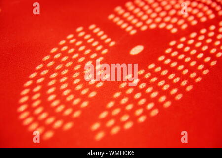 the sun's rays cast a disk shadow of circles. abstract shadows dots on a red background. seamless pattern of dots in white shades with polka dots. - Stock Photo
