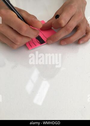 Cropped Hands Of Woman Scribbling On Sticky Note - Stock Photo