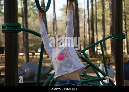 Girl Playing On Monkey Bars At Park - Stock Photo