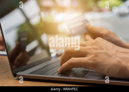 Cropped Hands Of Man Making Credit Card Payment Over Laptop On Table At Home - Stock Photo