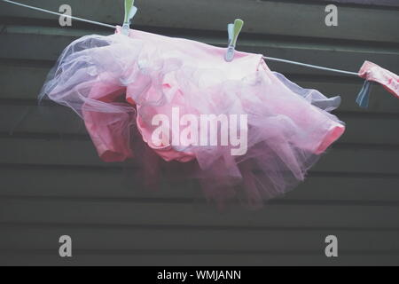 Low Angle View Of Pink Dress Hanging From String Against Wall - Stock Photo