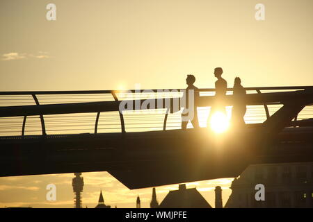 Silhouette People Walking On Bridge Against Sky During Sunset - Stock Photo