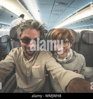 Cheerful adult caucasian couple taking selfie inside plane. Fish eye view from below. Concept of people traveling, natural light. - Stock Photo