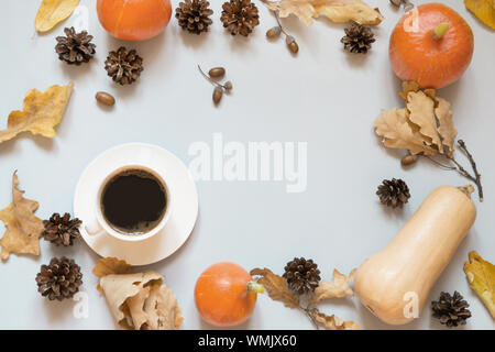 Fall still life, black coffee, dry colorful leaves and pumpkin on grey background. Top view and copy space. - Stock Photo
