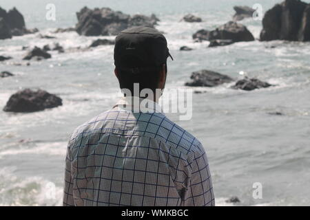 Rear View Of Man Wearing Cap At Beach During Sunny Day - Stock Photo