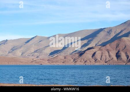 Scenic View Of Lake And Arid Mountains Against Blue Sky - Stock Photo