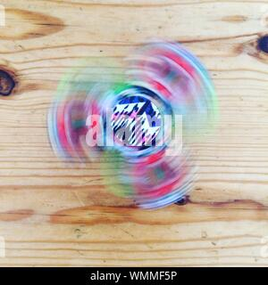 Directly Above Shot Of Colorful Illuminated Fidget Spinner Spinning On Wooden Table - Stock Photo