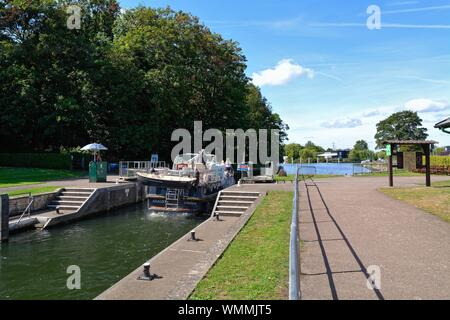 A river cruiser passing through Shepperton lock on a sunny summers day, Surrey England UK - Stock Photo