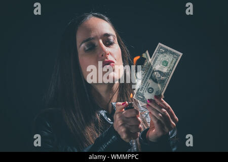 Close-up Of Woman Puckering Lips While Burning Dollar Note Against Black Background - Stock Photo