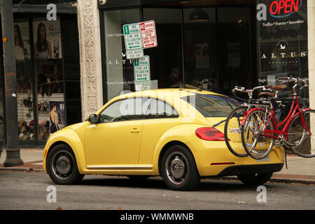 Yellow Volkswagen beetle in the city with bicycles on bike rack - Stock Photo