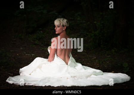 Bride Wearing Backless Wedding Dress Sitting In Forest - Stock Photo