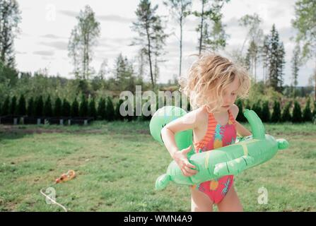 girl holding an inflatable, playing with water in the garden at home - Stock Photo