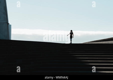 Silhouette of woman walking on stairs with blue sky in background - Stock Photo