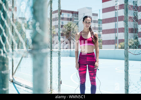 Colorful image of female athlete posing with jumping rope on court - Stock Photo