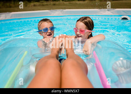 Mother floats on raft in pool with kids splashing at feet on sunny day - Stock Photo