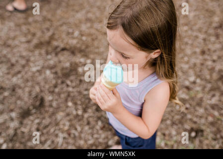 Close up of young girl eating a blue ice cream cone