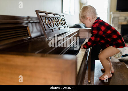 Baby boy in diaper stands on bench playing piano at home
