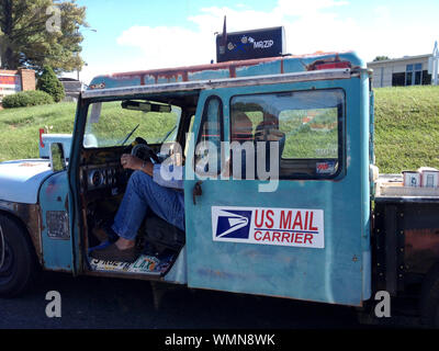 USPS  worker delivering the mail from an old truck in rural U.S.A. - Stock Photo
