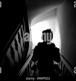 Rear View Of Woman Walking Down Stairs - Stock Photo