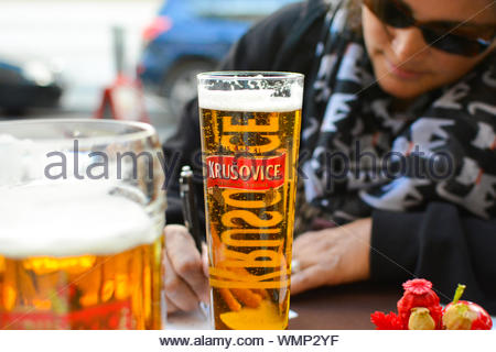 A woman wearing dark glasses and drinking a beer fills out postcards at a sidewalk cafe - Stock Photo